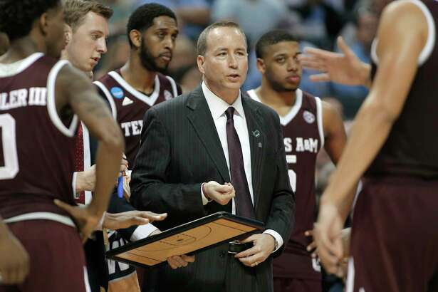 Texas A&M head coach Billy Kennedy, center, talks with his team during the first half of a second-round game against North Carolina in the NCAA men's college basketball tournament in Charlotte, N.C., Sunday, March 18, 2018. (AP Photo/Gerry Broome)