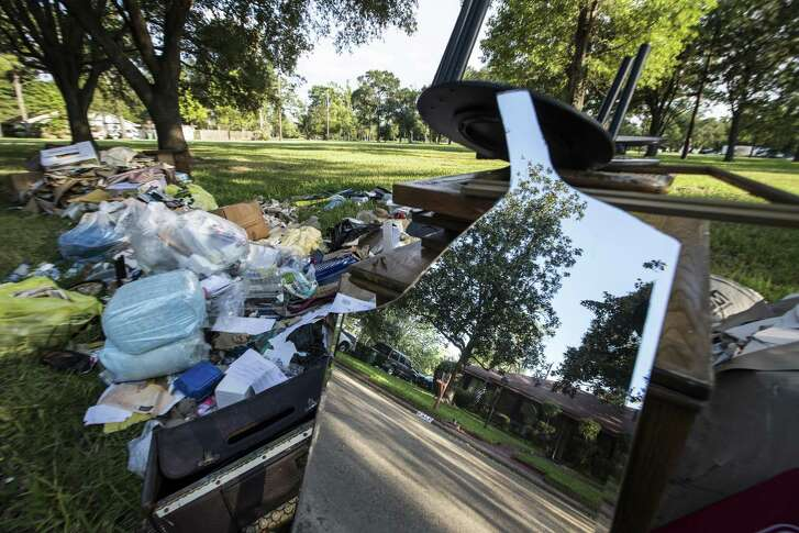 A home is reflected in a mirror on a debris pile in the Arbor Oaks neighborhood on Sept. 20, 2017, in Houston. The neighborhood used to be home to 160 houses and is now down to 13, after most of the homeowners, having flooded repeatedly, sold to the Harris County Flood Control District.