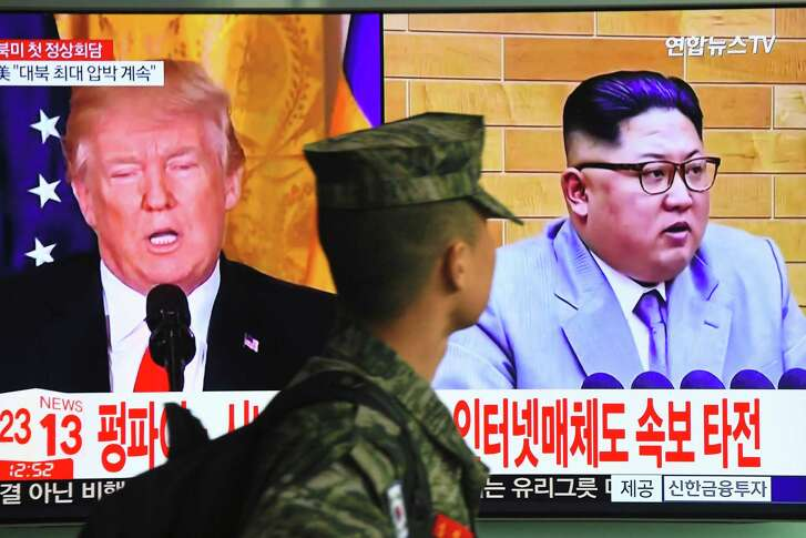 A South Korean soldier walks past a television screen showing pictures of President Donald Trump and North Korean leader Kim Jong Un at a railway station in Seoul on March 9, 2018. Trump agreed on March 8 to a historic first meeting with North Korean leader Kim Jong Un in a stunning development in America's high-stakes nuclear standoff with North Korea.