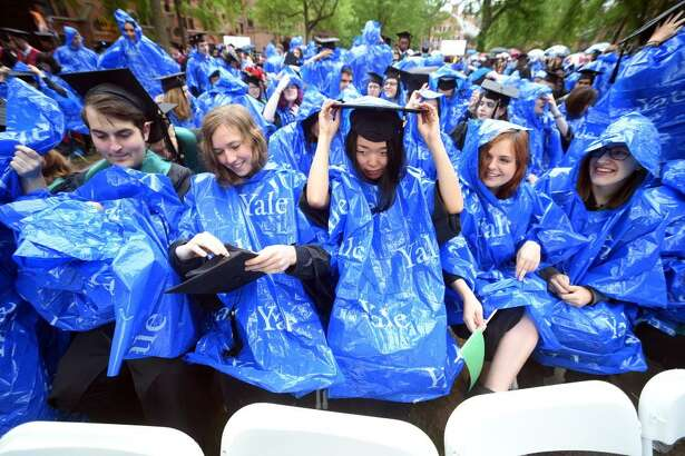 (Arnold Gold-New Haven Register)  Graduates put on rain ponchos as showers begin during Yale University Commencement on Old Campus in New Haven on 5/22/2017.