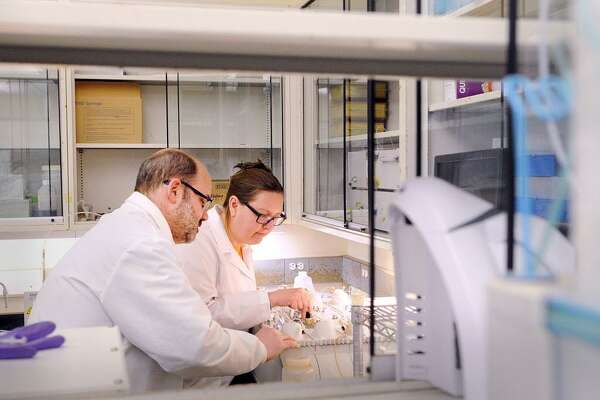 Director of the Laboratory for UConn's Center for Environmental Sciences and Engineering, Chris Perkins, left,  and Stephanie Kexel, a UConn lab manager, analyze a river water sample in the lab at the Center for Environmental Sciences and Engineering, Storrs, Conn., Wednesday, March 14, 2018. There is a fundraiser getting kicked off to raise money for an endowment fund to set-up Innis Arden Cottage at Greenwich Point as a major research center, led by UConn scientists, to study Western Long Island Sound.