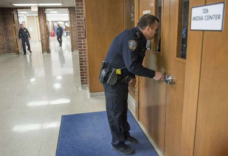 Resource Officer Tom Stumbo checks a door and tries to see inside the Media Center during a Lockdown exercise Feb. 23 at Lincoln East High School in Lincoln, Neb. Arming teachers will add to the dangers in school shootings, not diminish them. Photo: Eric Gregory /Associated Press / 2018 the Lincoln Journal Star