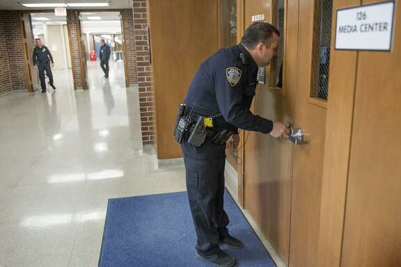 Resource Officer Tom Stumbo checks a door and tries to see inside the Media Center during a Lockdown exercise Feb. 23 at Lincoln East High School in Lincoln, Neb. Arming teachers will add to the dangers in school shootings, not diminish them.