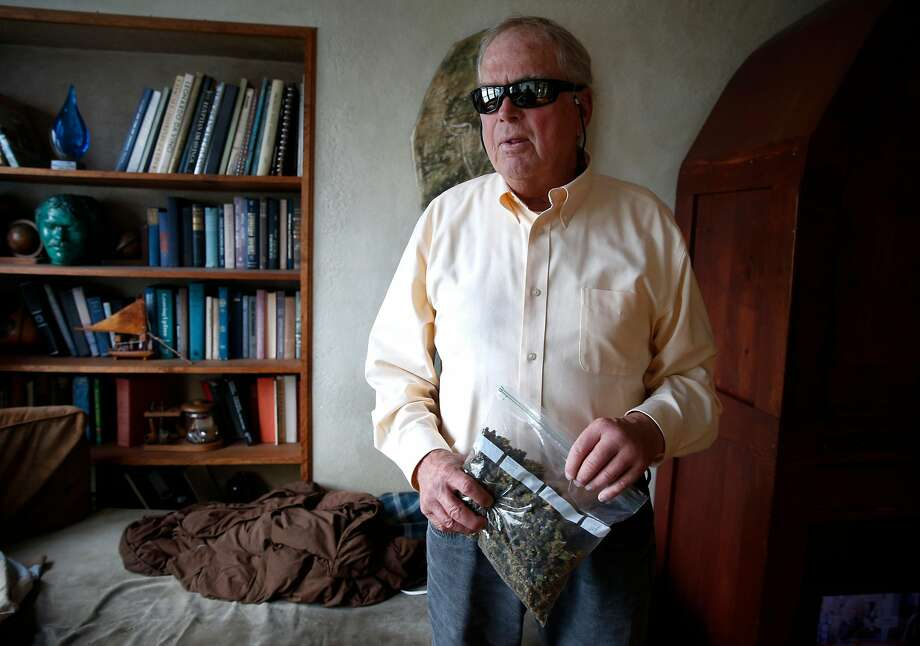 Ed Gallagher holds a baggie of medicinal cannabis at his Twin Peaks home in San Francisco. The blind former Army intelligence officer smokes marijuana to deal with various HIV-related problems and relies on charity for much of his food and medicine. Photo: Paul Chinn, The Chronicle