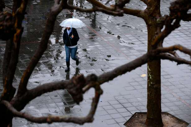 A student walks through Sproul Plaza in the rain at UC Berkeley on Friday, March 16, 2018. A series of storms continue to douse the Bay Area.