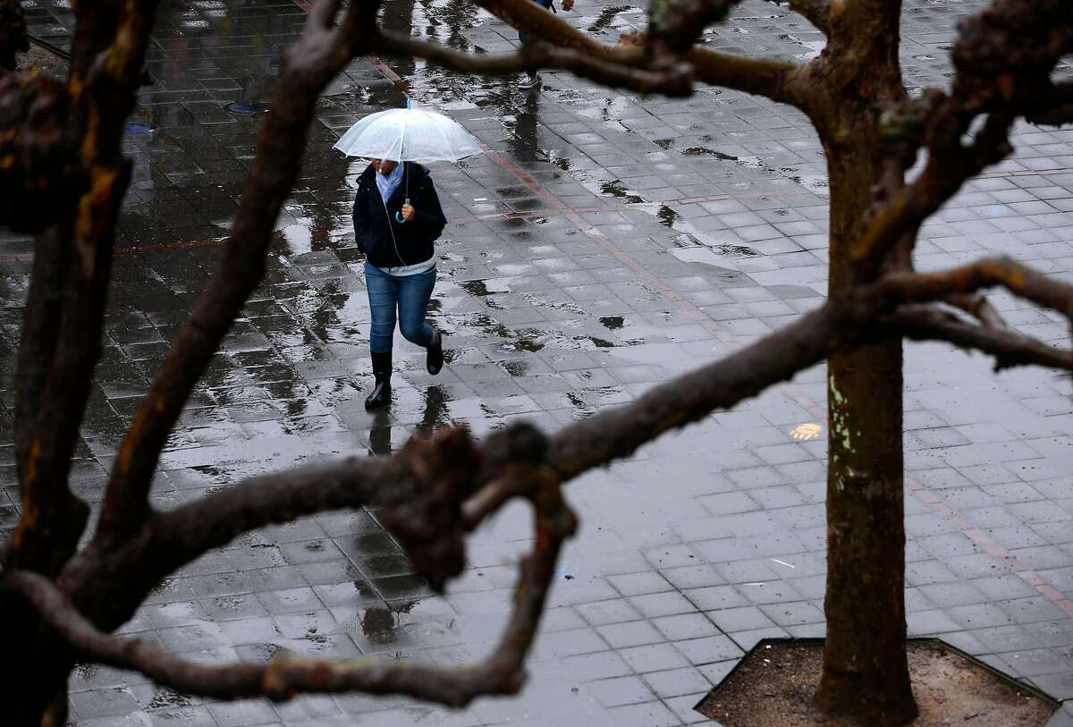 A student walks through Sproul Plaza in the rain at UC Berkeley on Friday, March 16, 2018. Despite recent rain,meteorologists say California will almost certainly emerge from the winter drier than normal.