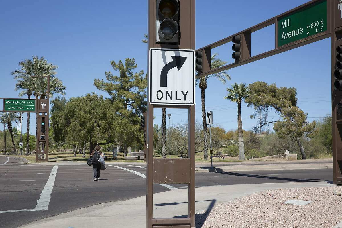 A woman crosses Mill Avenue at its intersection with Curry Road in Tempe, Ariz., March 19, 2018. A pedestrian, who was crossing the street outside of a crosswalk, was struck and killed by a self-driving Uber vehicle at the intersection a night earlier. (Caitlin O'Hara/The New York Times)