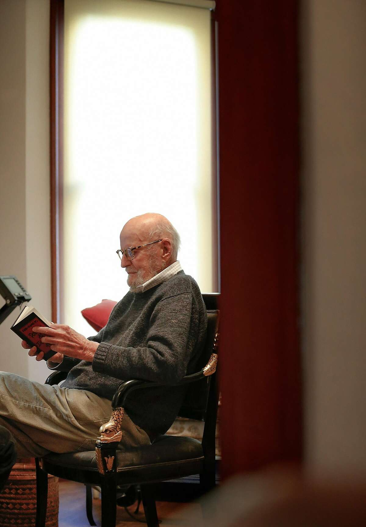 Poet Lawrence Ferlinghetti leafs through one of his books at his home in San Francisco, Calif., on Thursday, March 1, 2018. Ferlinghetti will be 99 on March 24.