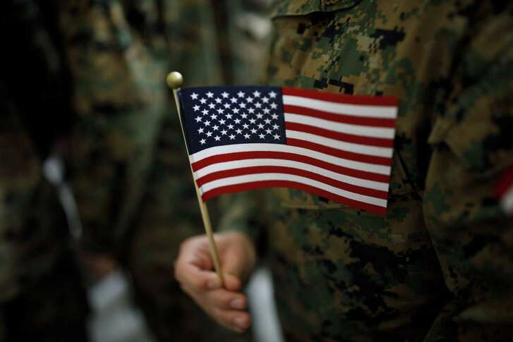 An attendee holds an American flag after an event with U.S. President Donald Trump, not pictured, at Marine Corps Air Station Miramar in San Diego, California, U.S., on Tuesday, March 13, 2018. Trump traveled to opposition territory -- California -- to fire up support for a wall along the U.S.-Mexico border, a project that has encountered resistance in Congress. Photographer: Patrick T. Fallon/Bloomberg