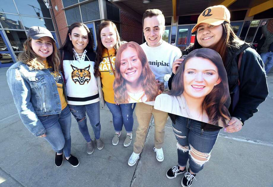 From left, Quinnipiac freshmen Brynn Martin, Caroline King, Katrina Manzari, Jonathan Sweeney and Camila Maturane are photographed in front of the TD Bank Sports Center before boarding a bus headed to Gampel Pavilion on Monday. They are holding photographs of their friends, Quinnipiac players Chiara Bacchini, left, and Danelle Bradley. Photo: Arnold Gold / Hearst Connecticut Media / New Haven Register
