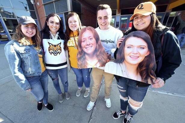 From left, Quinnipiac freshmen Brynn Martin, Caroline King, Katrina Manzari, Jonathan Sweeney and Camila Maturane are photographed in front of the TD Bank Sports Center before boarding a bus headed to Gampel Pavilion on Monday. They are holding photographs of their friends, Quinnipiac players Chiara Bacchini, left, and Danelle Bradley.