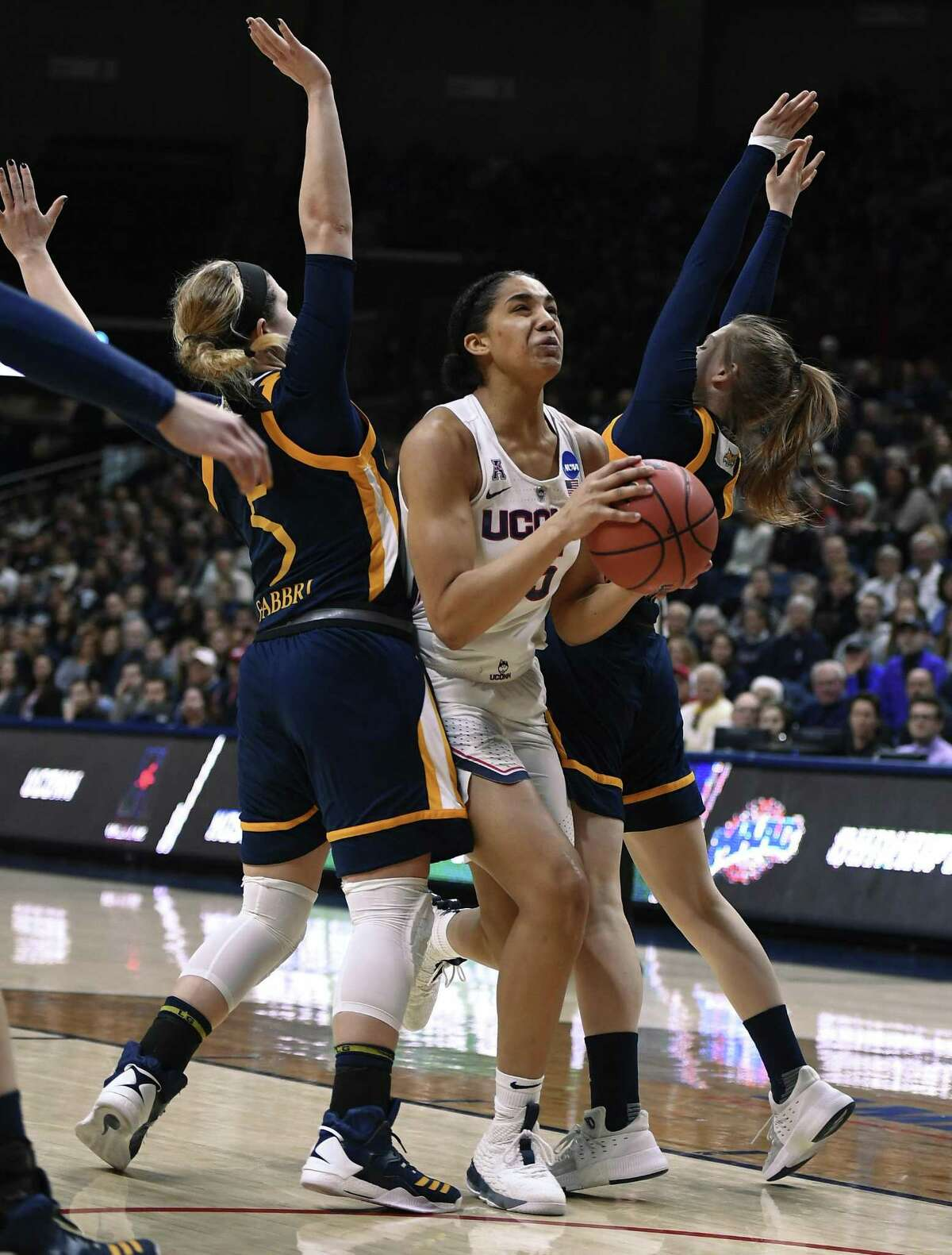 UConn's Gabby Williams, center, splits the defense of Quinnipiac's Carly Fabbri, left, and Edel Thornton Monday in Storrs.