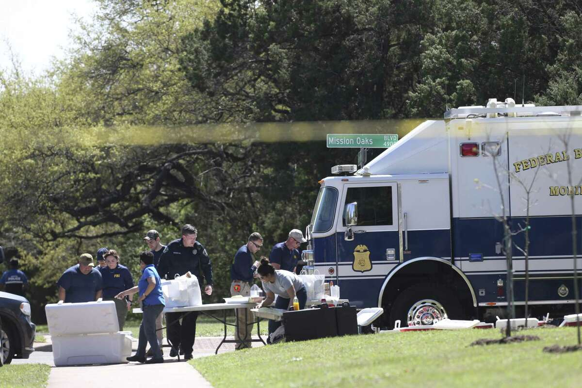 Law enforcement personnel break for lunch near the site of an explosion on the southwest side of Austin, Monday, March 19, 2018. Two men in their twenties were injured in an explosion set off by a trip wire Sunday night. It is the fourth such explosion in Austin in three weeks, leaving two dead and several injured.