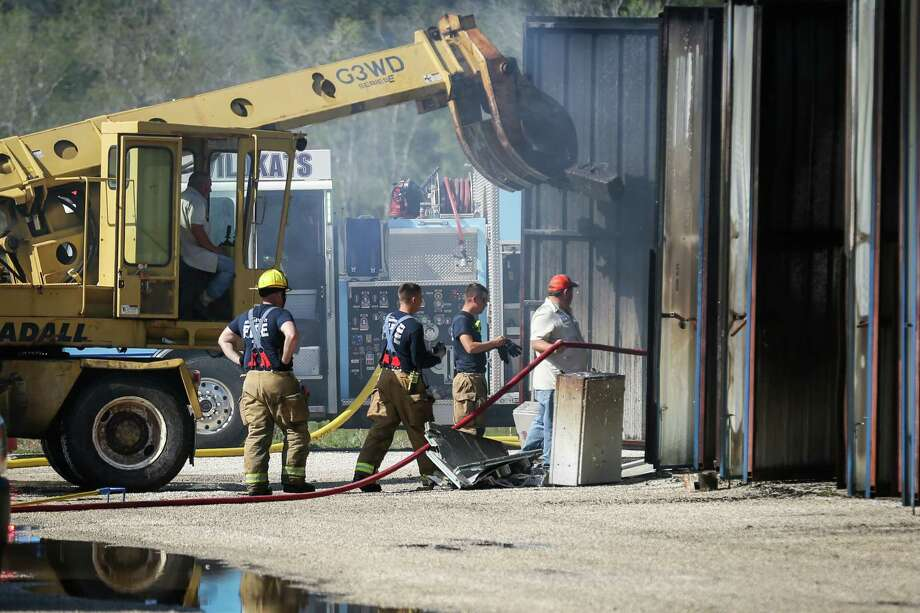 Firefighters extinguish the last remaining hotspots of a fire that destroyed 72 storage units on Monday at Piney Woods Boat and RV Storage in Willis. Photo: Michael Minasi, Staff Photographer / © 2018 Houston Chronicle