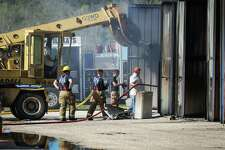 Firefighters extinguish the last remaining hotspots of a fire that destroyed 72 storage units on Monday at Piney Woods Boat and RV Storage in Willis.