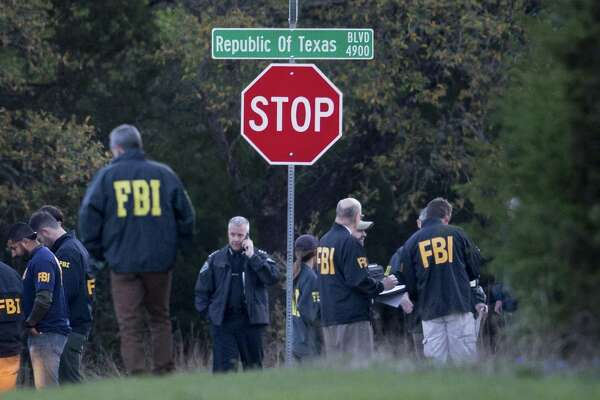 Law enforcement officers gather at the intersection of Republic of Texas and Mission Oaks boulevards in the the Travis Country neighborhood of Austin, Texas to investigate a bombing on Monday, March 19, 2018.