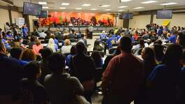 People crowd the room during a SAISD Board meeting in which the board appoved a contract with Democracy Prep Charter to operate Stewart Elementary School. A teacher lawsuit is challenging the action.