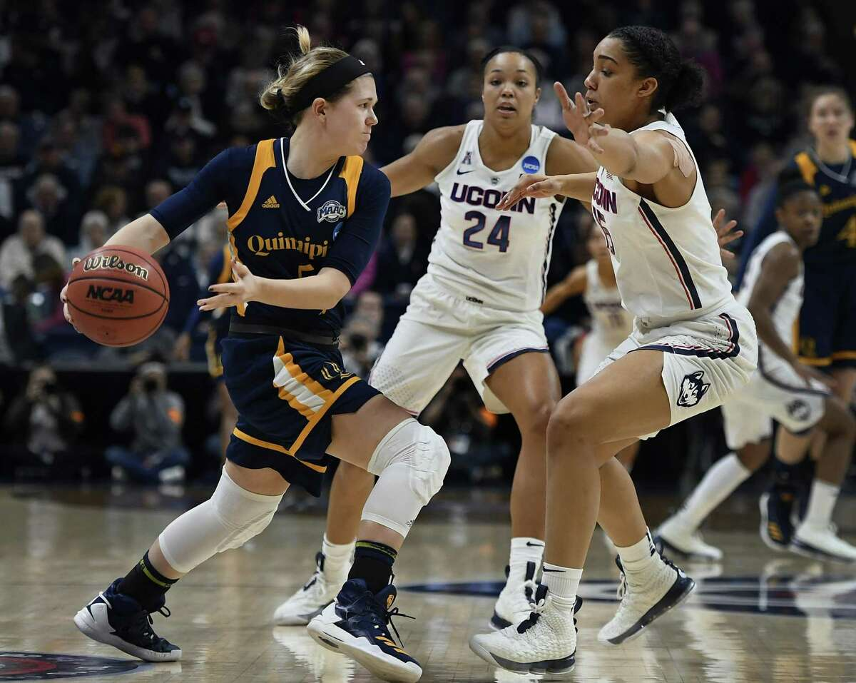Quinnipiac's Carly Fabbri, left, passes under pressure from UConn's Napheesa Collier, center, and Gabby Williams, right, during the first half of a second-round game in the NCAA Tournament on Monday in Storrs.