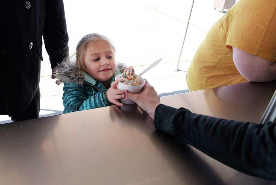 Madilynn Sano, 5, gets her vanilla ice cream with rainbow sprinkles during opening day at the Kurver Kreme on Monday, March 19, 2018, in Colonie, N.Y. This is the 66th year of operation for the ice cream stand. The stand will be open Monday through Friday from 11:00am to 9:00pm, Saturday Noon to 9:00pm and Sunday 1:00pm to 9:00pm. Kurver also has for the second year, Dole vegan frozen treat.  (Paul Buckowski/Times Union) Photo: PAUL BUCKOWSKI / (Paul Buckowski/Times Union)