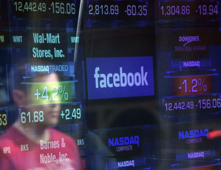 A Facebook logo is seen through the windows of the NASDAQ stock exchange. Facebook shares tumbled Monday.