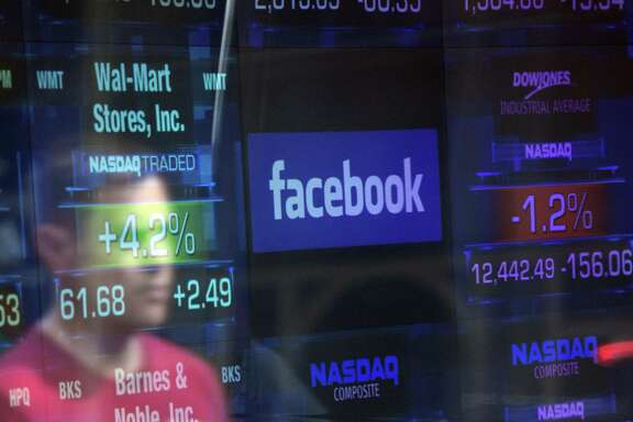 A Facebook logo is seen through the windows of the NASDAQ stock exchange. Facebook shares tumbled Monday.