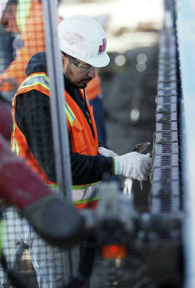 A mason completes finishing work as he follows SAM, a semi-automated mason, at work on the facade of a school in the south Denver suburb of Englewood, Colo. Photo: David Zalubowski / David Zalubowski / Associated Press / Copyright 2018 The Associated Press. All rights reserved.