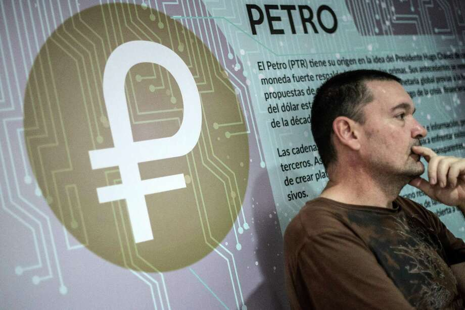 Signage describing the Petro cryptocurrency is displayed on a wall as a student listens inside the mining farm and school at the Ministry of Youth and Sports facility in Caracas, Venezuela. Photo: Carlos Becerra / Carlos Becerra / Bloomberg File / © 2018 Bloomberg Finance LP