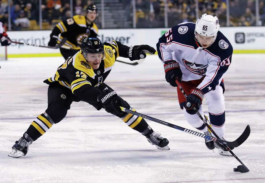 Boston Bruins forward Ryan Donato, left, tries to poke the puck away from Columbus Blue Jackets defenseman Markus Nutivaara (65) during the second period of an NHL hockey game in Boston, Monday, March 19, 2018. (AP Photo/Charles Krupa) Photo: Charles Krupa / Copyright 2018 The Associated Press. All rights reserved.