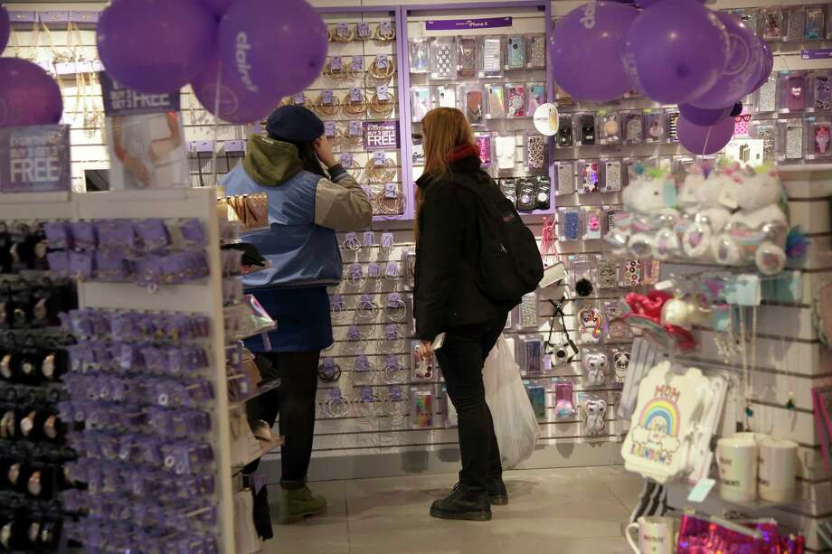 People shop at a Claire's in New York, Saturday, March 17, 2018. The mall chain that has pierced the ears of millions of teens has filed for Chapter 11 bankruptcy protection.  The accessories chain said Monday, March 19, 2018, that its stores will remain open as it restructures its debt. (AP Photo/Seth Wenig) Photo: Seth Wenig, Associated Press / Copyright 2018 The Associated Press. All rights reserved.