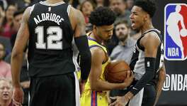 San Antonio Spurs' Dejounte Murray celebrates after a dunk around Golden State Warriors' Quinn Cook as teammate San Antonio Spurs' LaMarcus Aldridge looks on during second half action Monday March 19, 2018 at the AT&T Center.