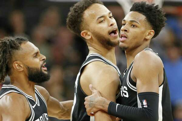 San Antonio Spurs' Patty Mills (from left), and Kyle Anderson celebrate with teammate Dejounte Murray after a dunk around Golden State Warriors' Quinn Cook (not pictured) during second half action Monday March 19, 2018 at the AT&T Center.