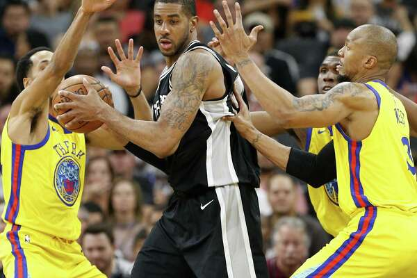 San Antonio Spurs' LaMarcus Aldridge looks for room between Golden State Warriors' Shaun Livingston (from left) Kevon Looney, and David West during second half action Monday March 19, 2018 at the AT&T Center.