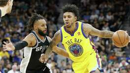 San Antonio Spurs' Patty Mills defends Golden State Warriors' Nick Young during second half action Monday March 19, 2018 at the AT&T Center.