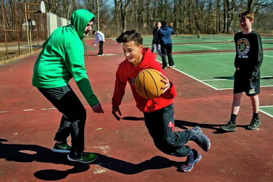Jefferson Middle School students Kayden Handsor, 12, center, and Cole Wright, 14, left, play basketball during The Rock after school program on Monday. Today marks the first day of spring, though temperatures are only expected to reach about 35 degrees. (Katy Kildee/kkildee@mdn.net)