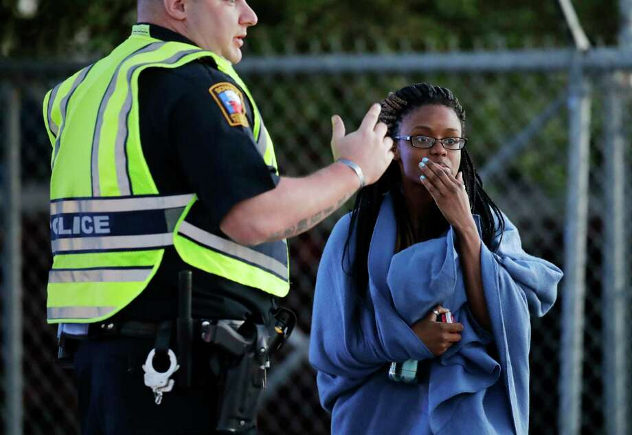 an employee wrapped in a blanket talks to a police officer after she was evacuated at