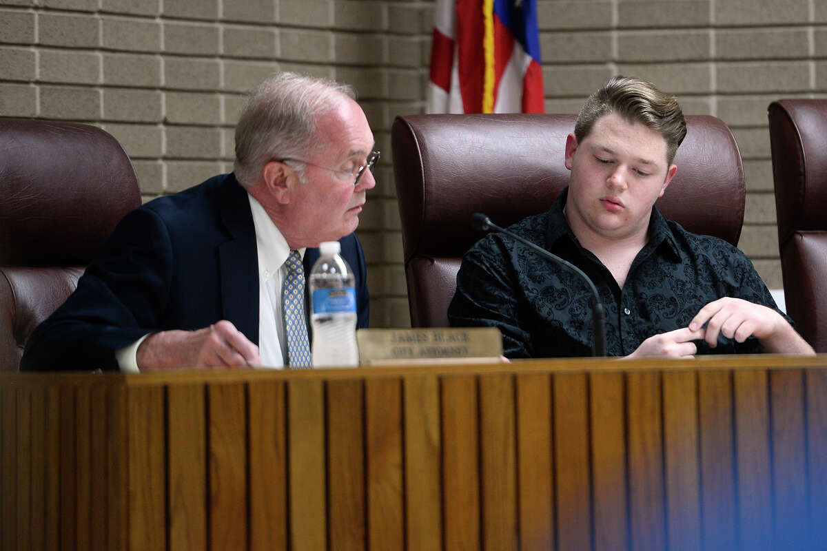 Groves City Attorney James Black, left, talks with councilman Cross Coburn during the city council meeting on Monday. Mayor Brad Bailey briefly addressed the topic of dating site photos of Coburn that were anonymously sent to the city and news outlets. Photo taken Monday 3/19/18 Ryan Pelham/The Enterprise