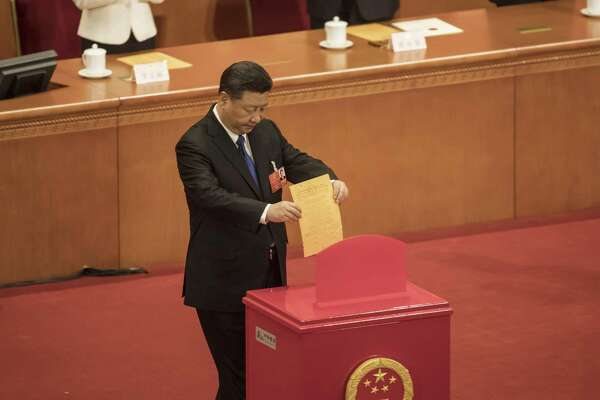 Chinese President Xi Jinping casts a ballot during a vote at a session at the first session of the 13th National People's Congress in Beijing on March 19, 2018.