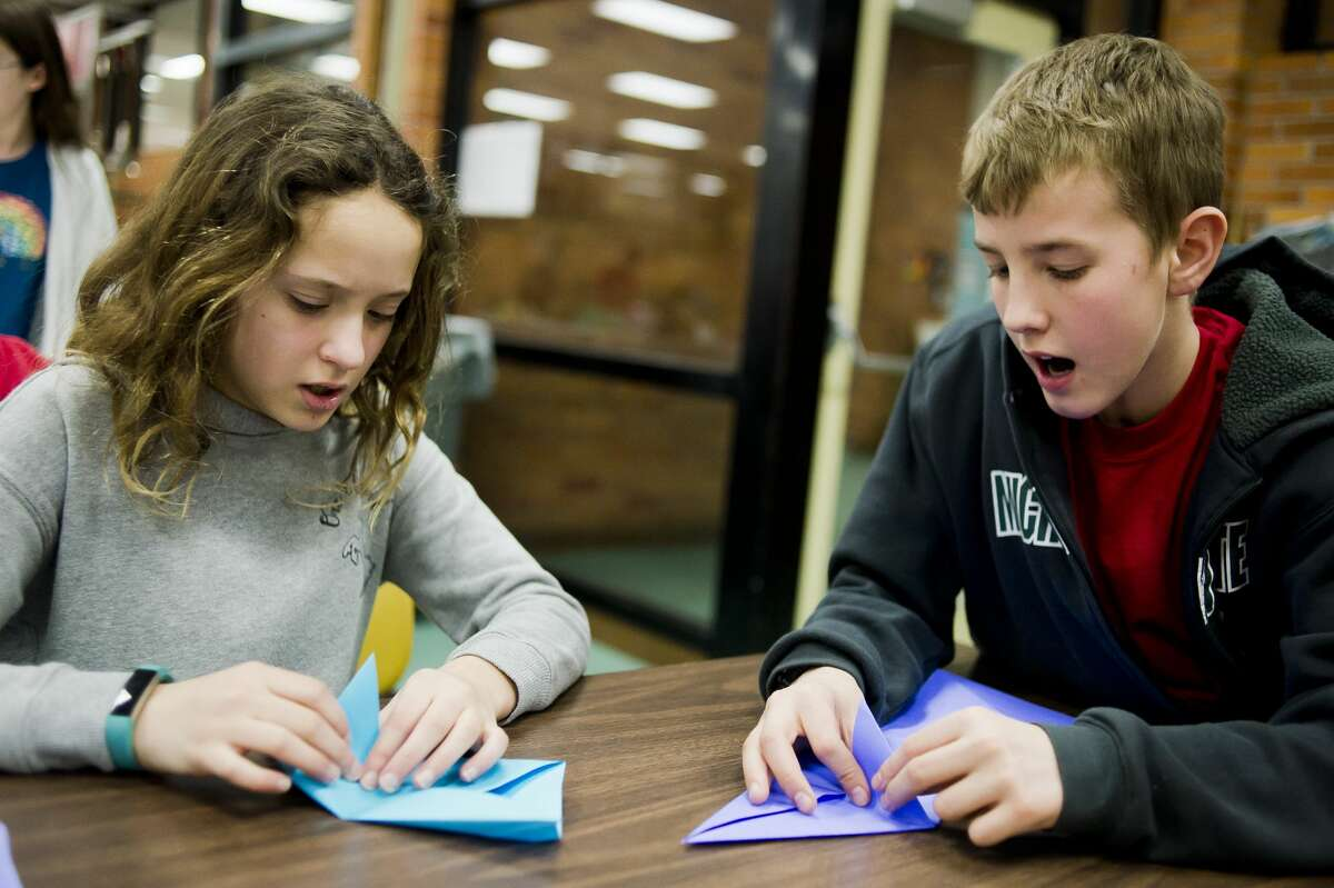 Jefferson Middle School students Zoe Gavin, 12, left, and James Barcia, 13, right, fold pieces of paper into origami seahorses during The Rock after school program on Monday, March 19, 2018. (Katy Kildee/kkildee@mdn.net)