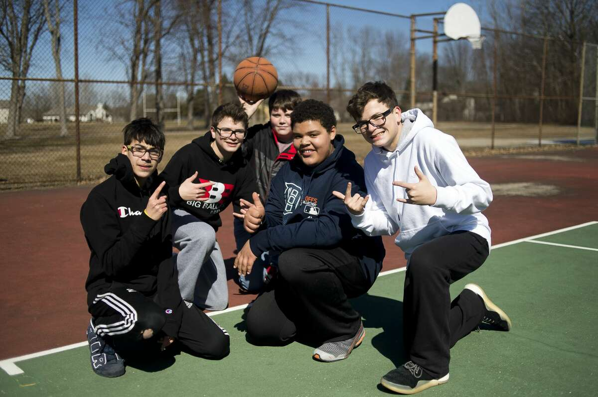 From left, Jefferson Middle School students Charles Raw, 14, Jake Rettelle, 14, Nathan Green, 14, Kyan Harper, 13, and Mike Rettelle, 14, pose for a photo while playing basketball during The Rock after school program on Monday, March 19, 2018. (Katy Kildee/kkildee@mdn.net)