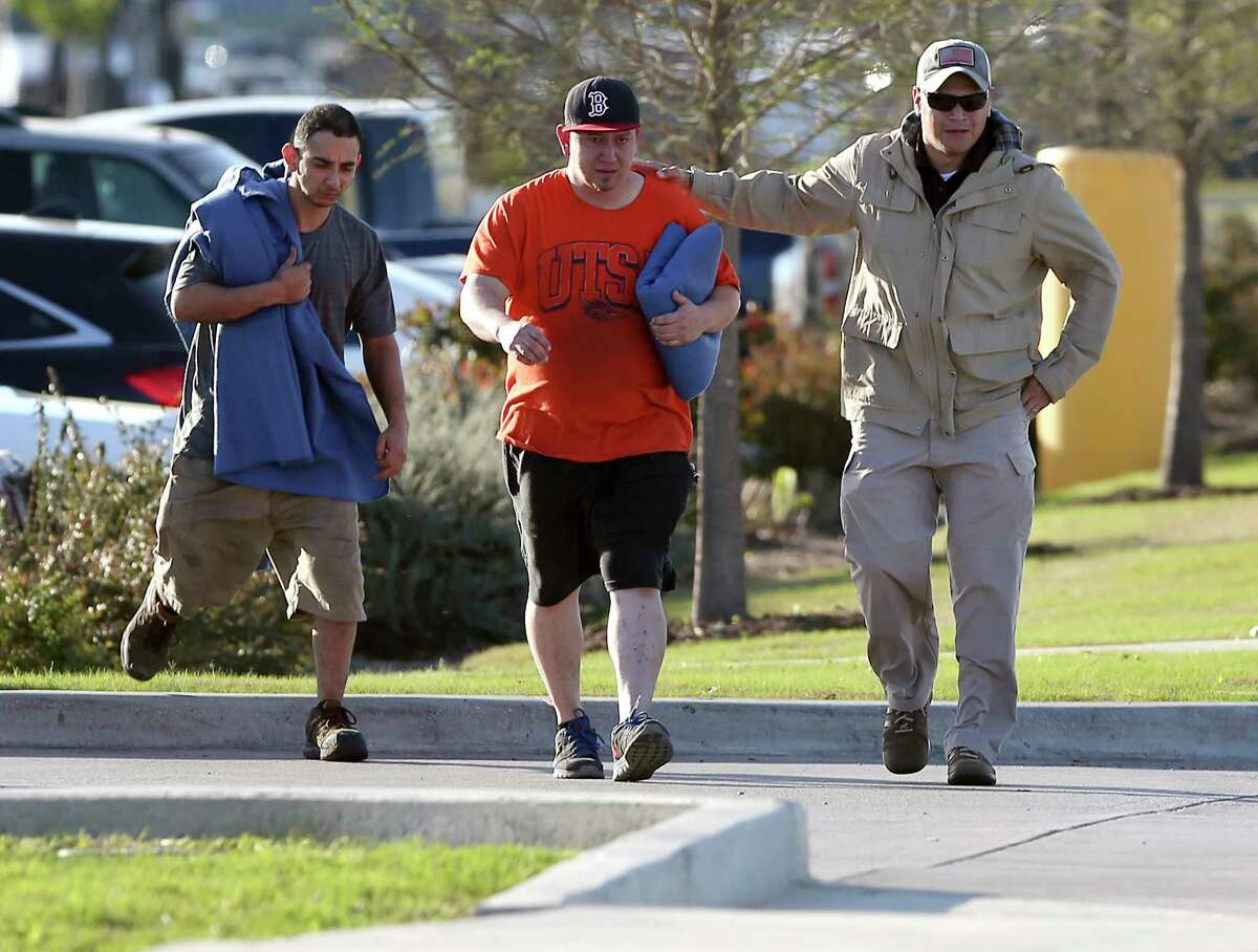 Two employees, left, who did not want to give their names leave the scene with a third man, right, who also did not want to give his name, Tuesday morning March 20, 2018 of a package bomb explosion at the FedEx ground shipping facility in Schertz. Officials have said the bomb appeared to be related to the four recent package explosions in Austin.
