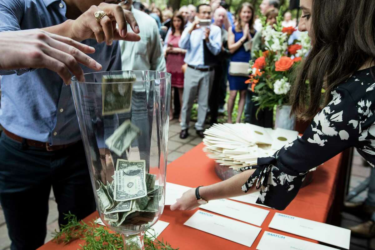 Fourth year medical students drop dollar bills into a jar as they receive their residency envelopes during the Match Day ceremony at McGovern Medical School at UTHealth on Friday, March 16, 2018, in Houston. More than 225 McGovern Medical School students found out where they will do their residency, as part of the results of the National Resident Matching Program.