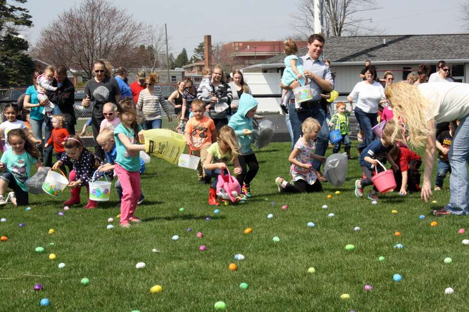 This file photo shows children scooping up Easter eggs during a local hunt last year. Photo: Tribune File Photo
