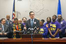 Governor Dannel P. Malloy (center) gave his support for a new contract for home care workers that would raise their minimum pay to $16.25 by 2020 at a press conference at the Capitol in Hartford, Conn. on Tuesday, March 20, 2018. Malloy was joined by home workers from the Local 1199 of the Service Employees International Union and a bipartisan group of legislators.