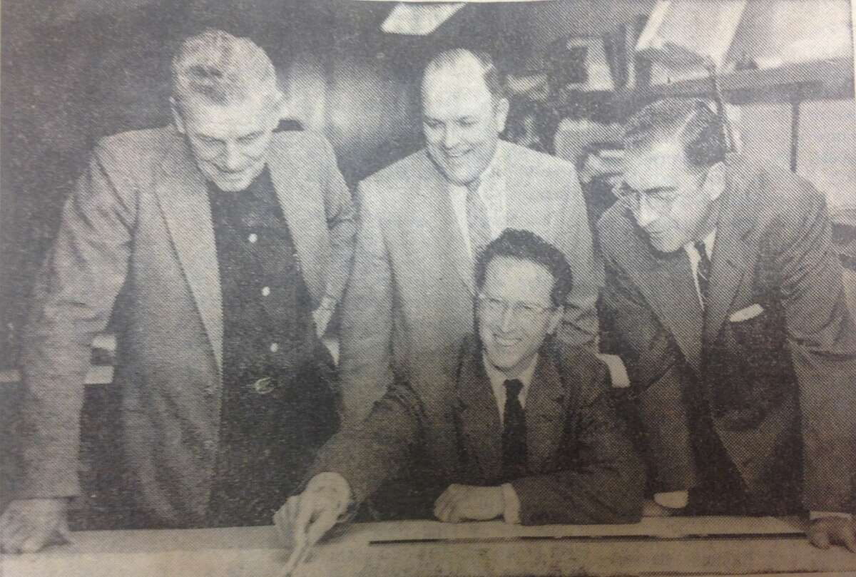 Now that Midland's campaign for a new stadium is in full swing, Cle Allison, seated, architect with the firm of Alden B. Dow, Inc., is receiving lots of encouragement to expedite the engineering drawings for the stadium. Checking over the progress with himon April 23, 1958, are, standing from left to right, Jim Barclay, athletic director for Midland Public Schools, Harper Camp, chairman of the stadium Size and Design committee, and William Dixon, campaign vice-chairman. Bids are expected to be let on the new stadium by the middle of May.