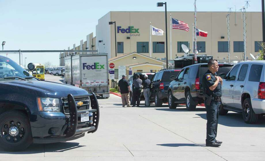 Federal officials, background, investigate the scene Tuesday morning March 20, 2018 of a package bomb explosion at the FedEx ground shipping facility in Schertz as a police officer secures the entrance to the facility. Officials have said the bomb appeared to be related to the four recent package explosions in Austin. Photo: William Luther, San Antonio Express-News / © 2018 San Antonio Express-News