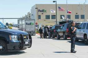Federal officials, background, investigate the scene Tuesday morning March 20, 2018 of a package bomb explosion at the FedEx ground shipping facility in Schertz as a police officer secures the entrance to the facility. Officials have said the bomb appeared to be related to the four recent package explosions in Austin.