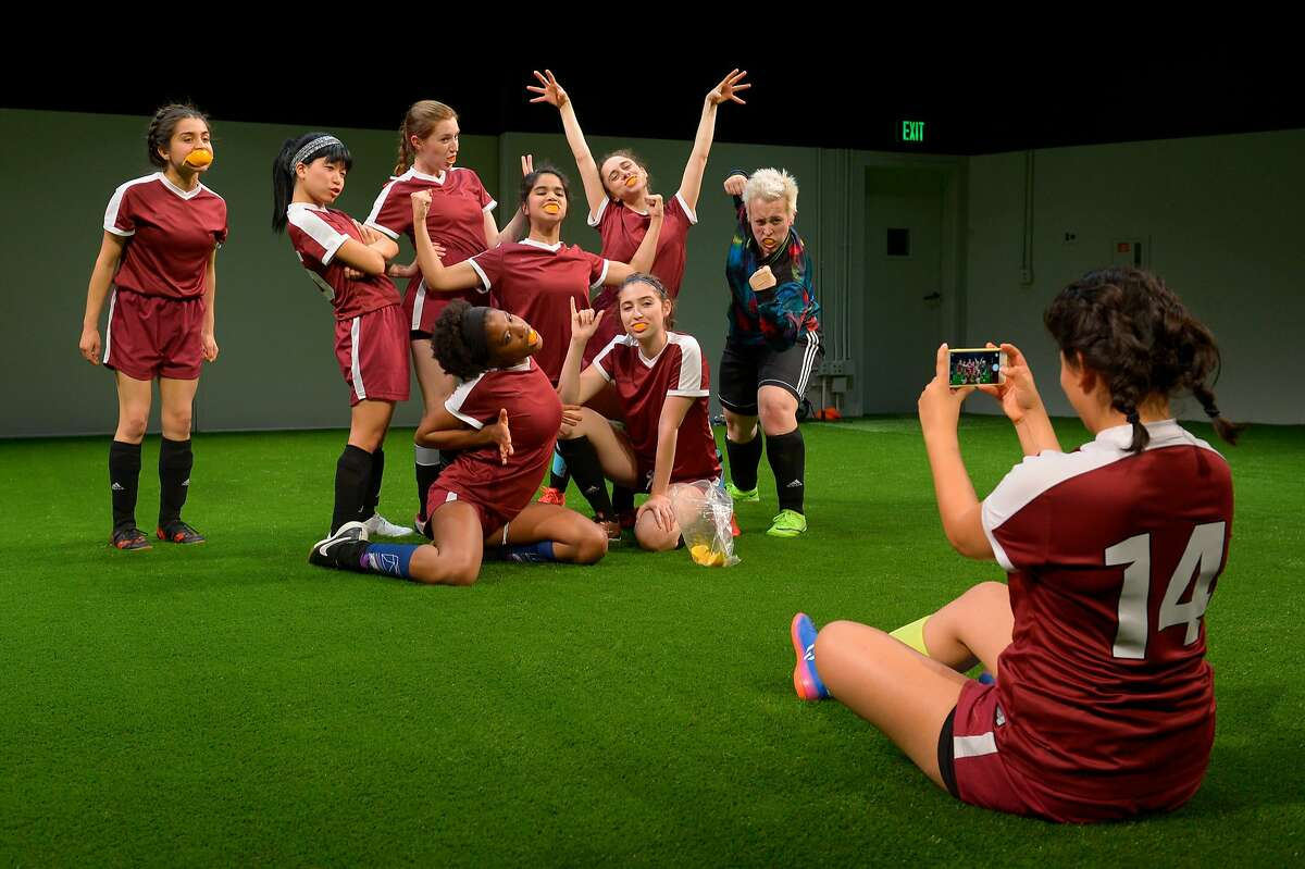 """From left:��Neiry Rojo as #46, Sango Tajima as #25, Isabel Langen as #2, Portland Thomas as #11, Nicole Apostol Bruno as #13, Emma Roos as #7, Carolyn Faye Kramer as #8, Betsy Norton as #00 Goalie and Jannely Calmell as #14�take a selfie with orange slices in Marin Theatre Company's """"The Wolves."""""""