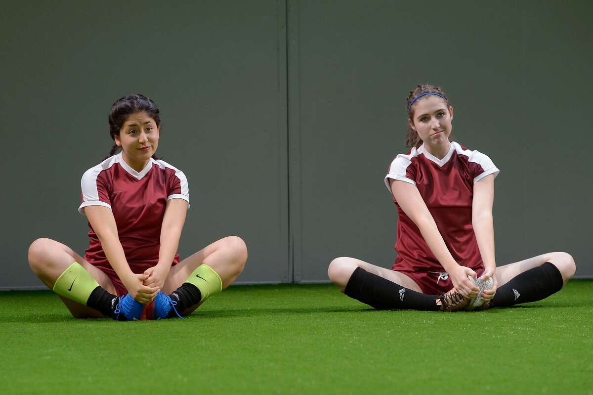 """From left: Jannely Calmell as #14 and Emma Roos as #7 warm up for a game in Marin Theatre Company's """"The Wolves."""""""