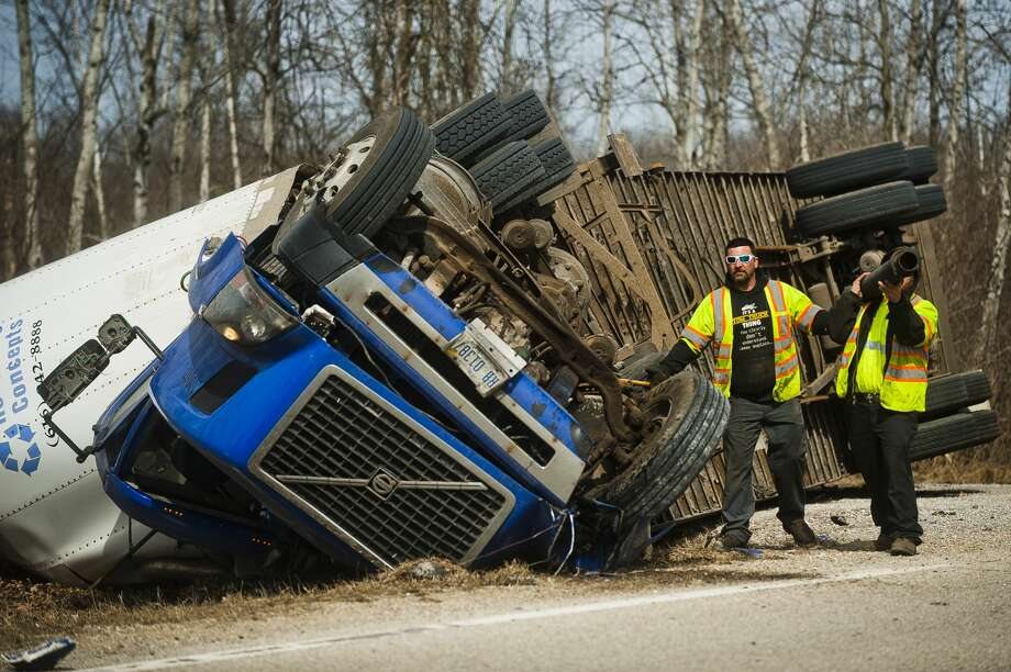 A crew from Mike's Wrecker Service prepares to right a tractor-trailer after it flipped while driving on W. Pine River Road near Porter Road on Tuesday, March 20, 2018 in Midland County. (Katy Kildee/kkildee@mdn.net) Photo: (Katy Kildee/kkildee@mdn.net)