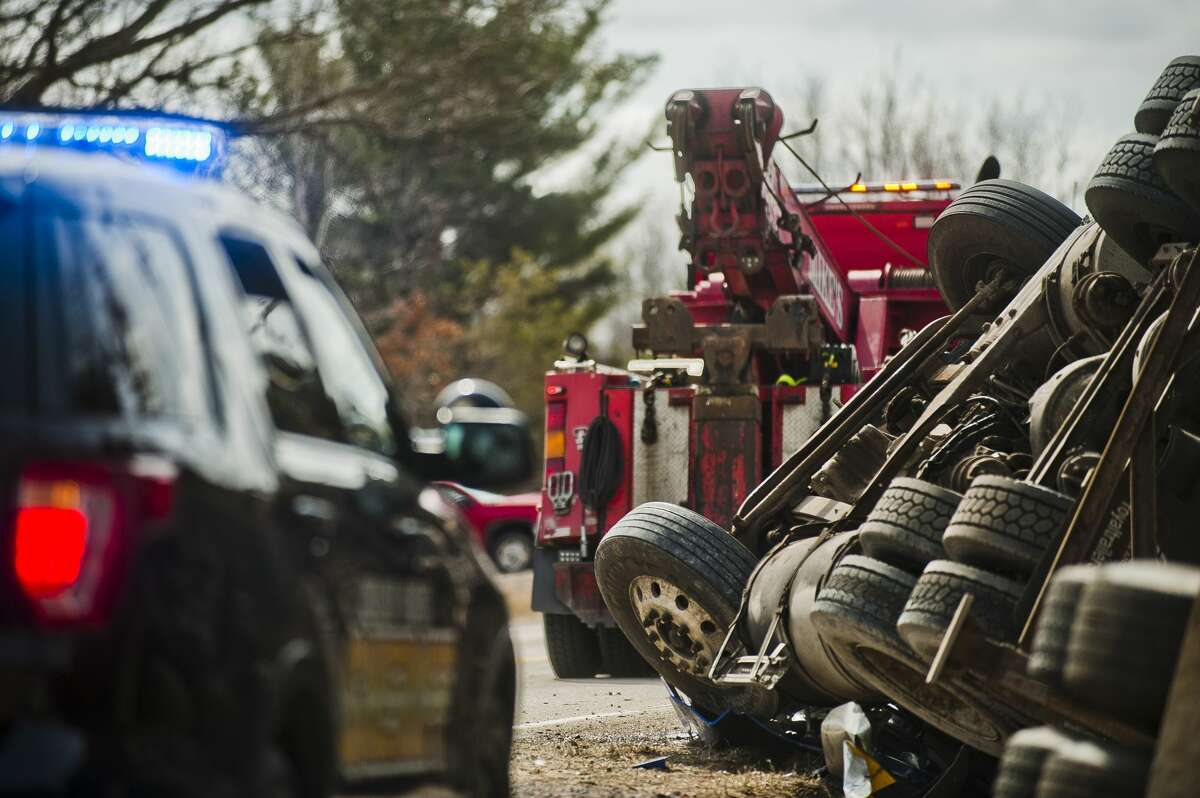 A crew from Mike's Wrecker Service prepares to right a tractor-trailer after it flipped while driving on W. Pine River Road near Porter Road on Tuesday, March 20, 2018 in Midland County. (Katy Kildee/kkildee@mdn.net)
